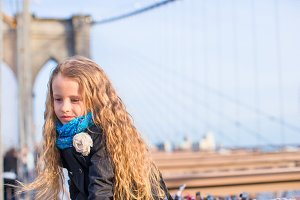 Adorable little girl sitting at Brooklyn Bridge with view on the road