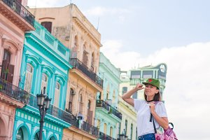 Young woman in popular area in old Havana, Cuba. Beautiful girl traveler background colorful houses in the city