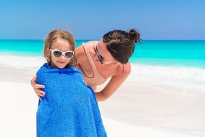 Happy family of mother and kid on the beach vacation. Little girl in towel on the seashore