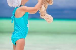 Adorable little girl with her favorite toy on tropical beach vacation