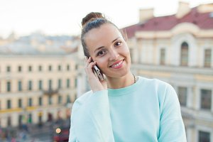 Cute businesswoman in glasses talking on phone and smiling while standing on the roof of the house in the old town