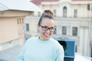 Cute businesswoman in eyeglasses talking on the phone standing on the roof of the house in the old town. Next to it are a laptop, smartphone and paper documents
