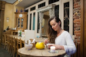 Attractive and lonely girl sitting in a cafe, drinking tea from the yellow teapot
