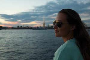 Young and beautiful girl sitting on the embankment of the river. she looks at the sunset and ships passing by. Saint Petersburg, Russia