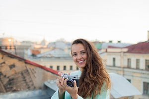 Fashion look, pretty cool young woman model with retro film camera. curly hair outdoors. Stylish girl photographer takes the old city from the roof at sunset