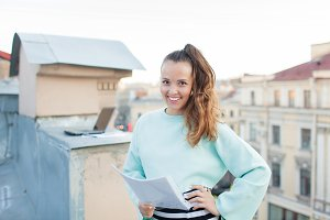 Attractive and stylish business woman holding a document and smiling while standing on the roof of the house in the Old town