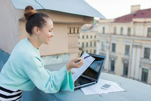Attractive and stylish businesswoman prepares documents for the roof of the house in the old town standing behind a laptop