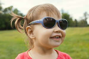 Little girl in sunglasses playing in park in front of green grass