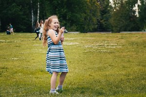 Smiling child girl wearing blue summer dress is playing in park