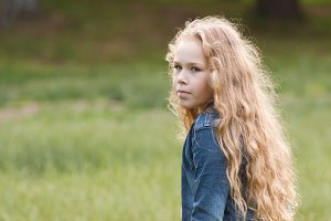 Little girl with curly hair feeling sadness - outdoor portrait