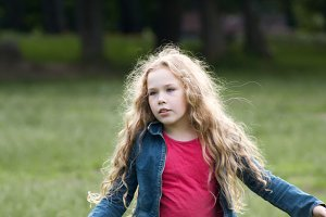 Pretty curly smiling child wearing jeans jacket in park