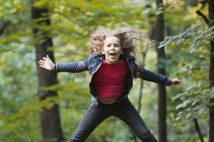 Little smiling girl child wearing jeans jacket - is jumping in park