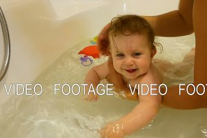Newborn baby playing and smiling in the bath