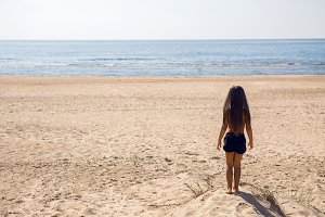 girl child standing on a sandy beach