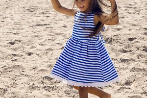 baby girl with long hair in striped blue dress