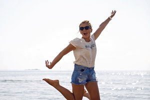 girl in sunglasses and short shorts jumping