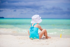 Little girl play with beach toys during tropical vacation