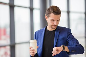 Urban man with coffee inside in airport. Casual young boy wearing suit jacket. Caucasian man with cellphone at the airport while waiting for boarding
