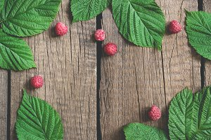 Old village boards Summer background with raspberry and leaves. flat lay with copy space
