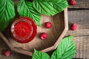 Homemade raspberry jam in a jar and fresh berries