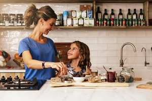 Little girl cooking with her mother.