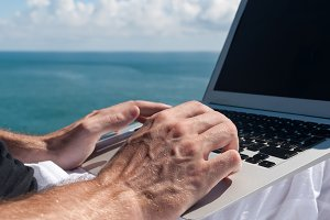 Male hands typing on a laptop with seascape background