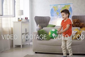 energetic kid boy play football and do sport exercises at home because of healthy lifestyle