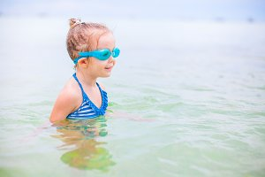 Adorable little girl swim in the sea on tropical beach vacation