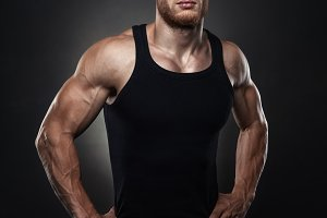 Portrait of a muscular male model against black background