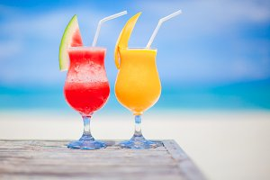 Two cocktails of watermelon and mango on background of stunning turquoise sea