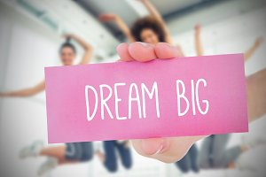 Woman holding pink card saying dream big