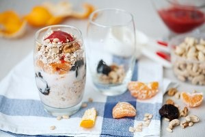 Yogurt oat granola with berries, mandarin and nuts in glass jars