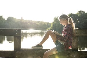 girl reading a book at the lake