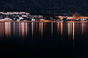 Night Tromso community with lights reflections background