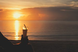 Man sitting on the beach and drinking cocktail during sunset