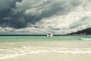 Exotic beautiful marine beach in Thailand with boat on blue water and stormy clouds sky
