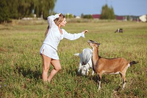 Woman stroking domestic goat.