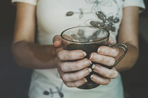 hands of woman with black coffee mug