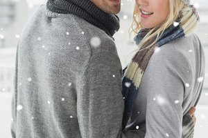 Composite image of cute couple in warm clothing hugging smiling at camera