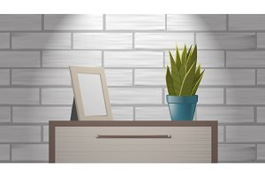 Realistic woden picture frame mock up and green home plant standing on commode.