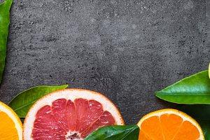 Fresh citrus fruit assortment on black.