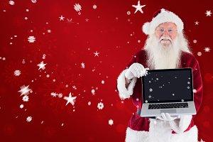 Composite image of santa claus presents a laptop