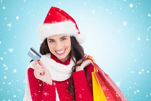 Composite image of excited brunette holding shopping bags and credit card
