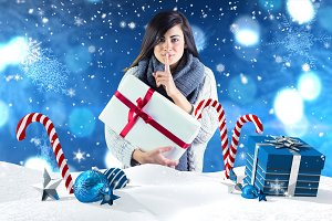 Composite image of brunette holding gift and keeping a secret