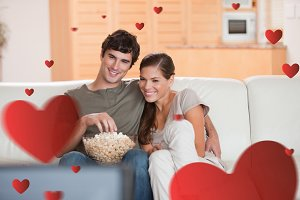 Composite image of couple with popcorn on the sofa watching a movie