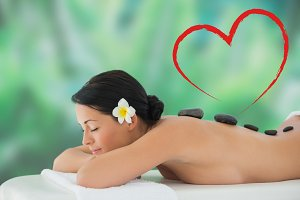 Composite image of beautiful brunette relaxing on massage table