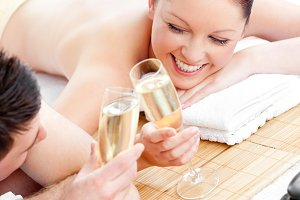 Composite image of loving young couple drinking champagne lying on a massage table