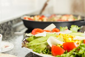 Fresh salad dish and cooking pan