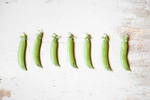 Pea pods on white wooden background