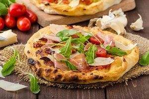 Italian pizza with parmesan cheese, prosciutto and arugula